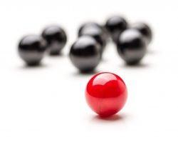 Symbolfoto zum Thema Leitung: Im Fokus steht eine rote Kugel vor sieben schwarzen Kugeln im Hintergrund