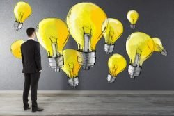 Symbolfoto für Kreativität und Design Thinking: Mann steht vor einer Wand mit gelben Glühbirnen im Comic-Stil