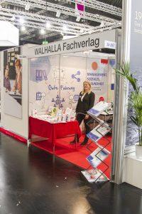 ConSozial 2017: Eine Mitarbeiterin präsentiert den Stand des Walhalla Fachverlages freundlich