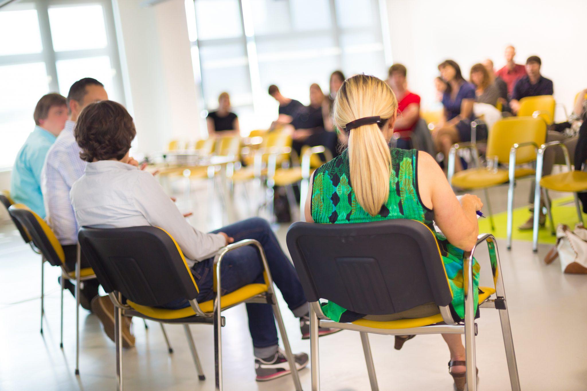 Redner sitzen im einem Stuhlkreis vor Publikum