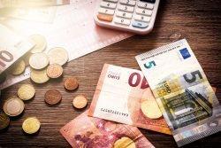 Symbolbild Euro-Scheine und Münzen liegen auf einer Rechnung