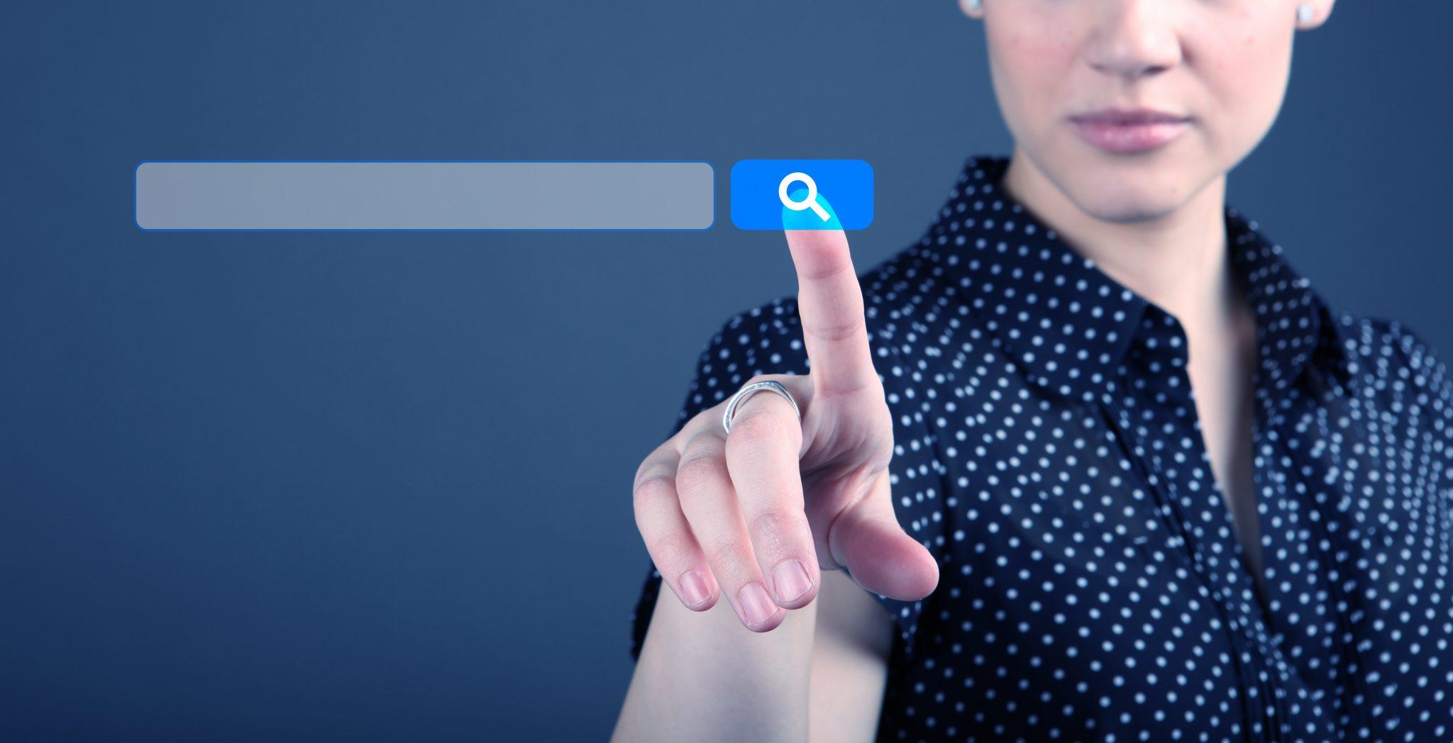 Symbolbild Internetsuche: Eine Frau tippt auf ein Suchsymbol.