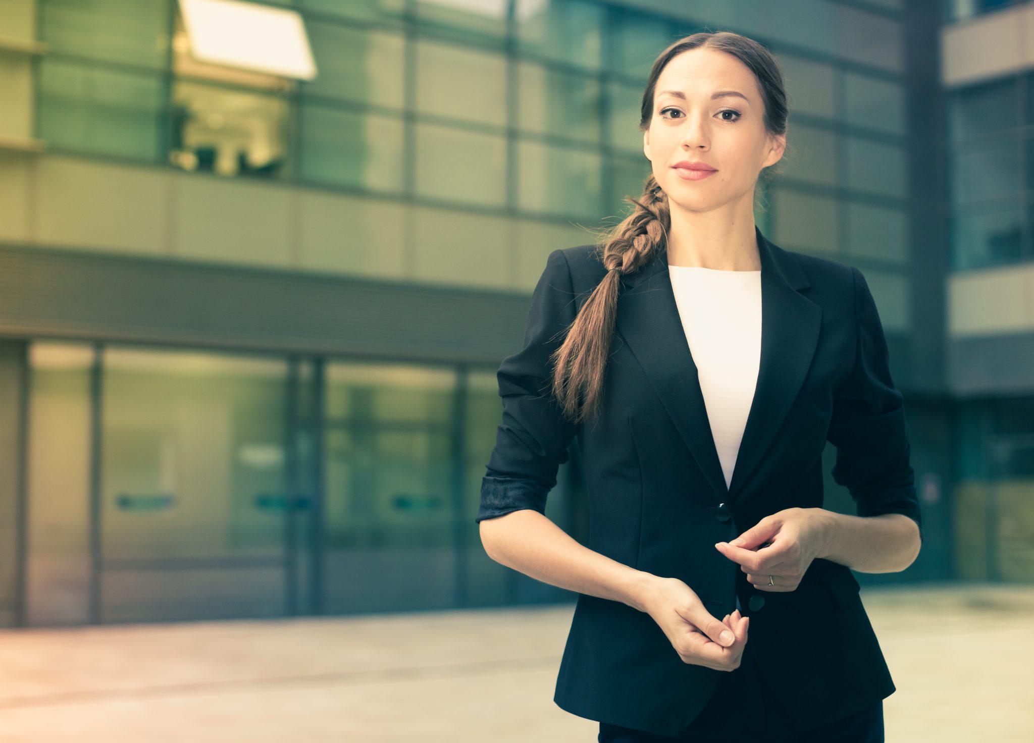 Junge Frau im Anzug steht vor einem Bürogebäude