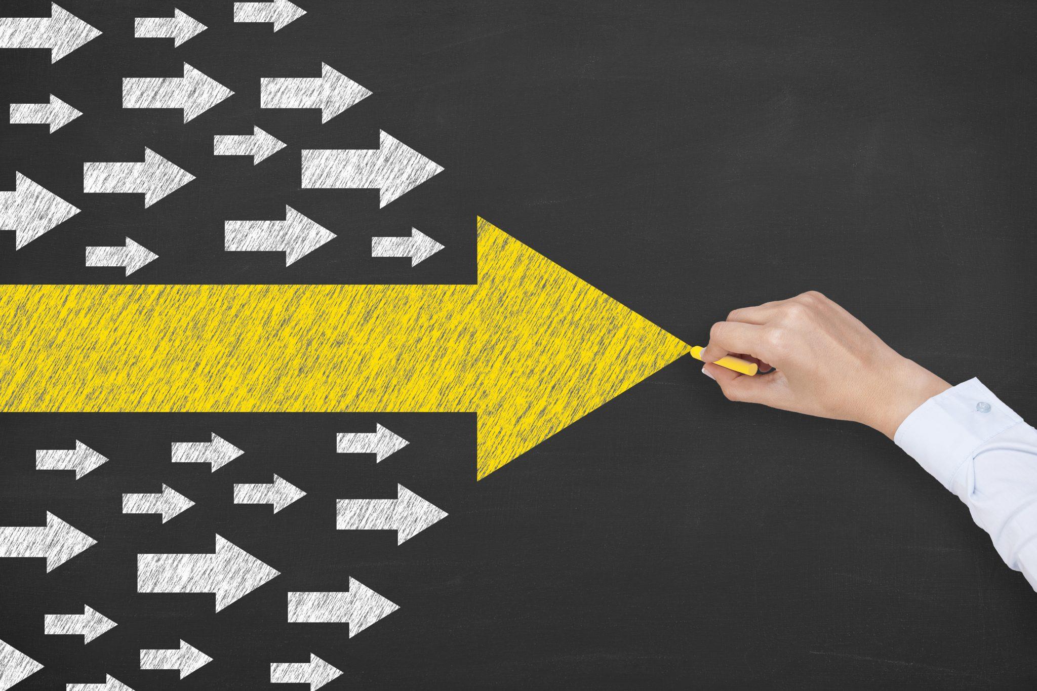 Symbolbild Führungskraft: Pfeile auf einer Kreidetafel