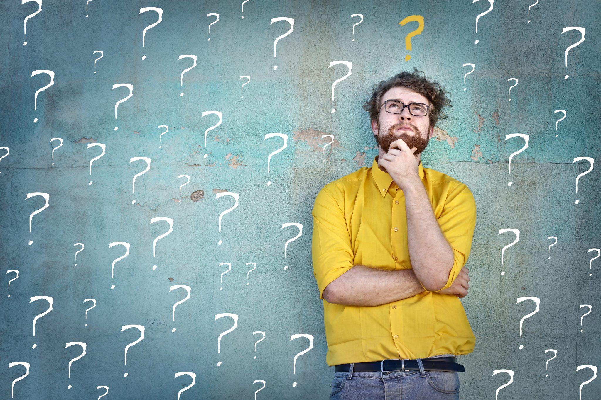 Ein junger Mann steht vor einer Betonwand mit Fragezeichen