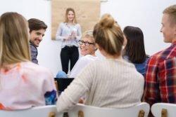 Teilnehmer in einem Vortrag schauen lächelnd über die Schulter zurück.