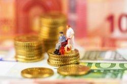 Symbolbild zum Mindestlohn: Figur eines Rollstuhlfahres und Pflegers auf einem Münzstapel