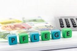 Symbolbild Pflege: Das Wort Pflege ist aus blauen und grünen Buchstabenwürfeln vor Geldscheinen und einem Taschenrechner zusammengesetzt.