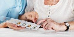 Pflegerin versorgt Seniorin mit Tabletten