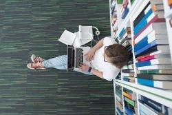 Studentin sitzt in einer Bibliothek an einem Bücherregal und arbeitet mit einem Laptop