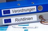 Zwei aufeinander gestapelte Odner sind mit dem EU-Logo und den Aufschriften Verordnungen und Richtlinien etikettiert