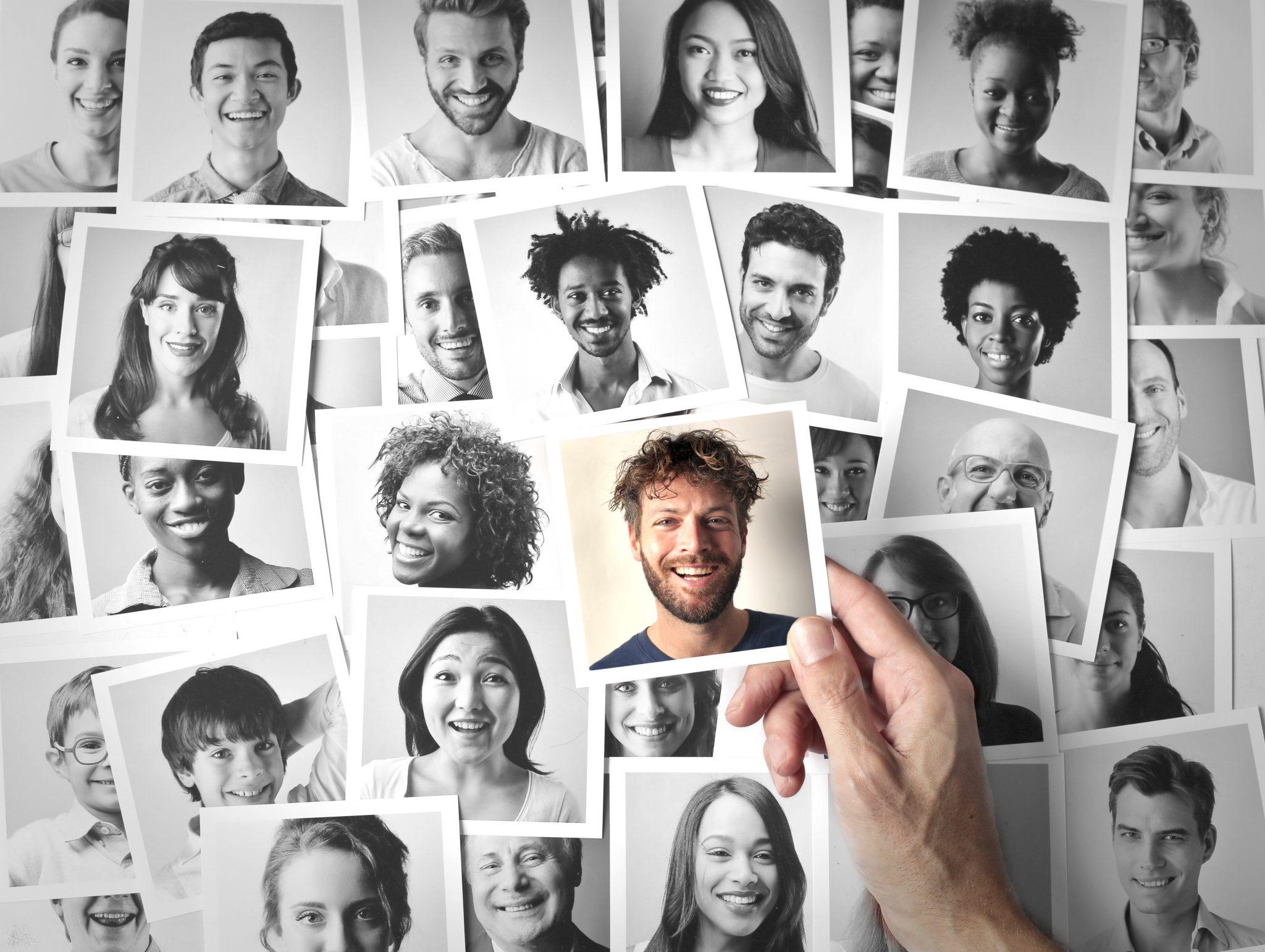 Symboldbild - Eine Hand wählt ein farbiges Foto aus einer Collage von Polaroidfotos verschiedener Menschen in schwarz-weiß aus.