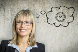 Frau im Businessoutfit lächelt in die Kamera. Eine gezeichnete Gedankenblase mit einer Uhr schwebt neben ihrem Kopf.