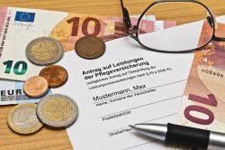 Symbolbild: Münzen und Scheine sind um einen Antrag auf Leistungen der Pflegeversicherung drapiert.