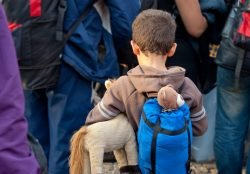 Kind mit Rücksack in einer Menschenmenge